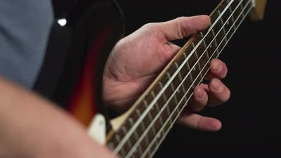 Playing on the fretboard of a bass guitar