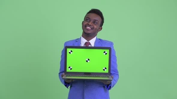 Thumbnail for Happy Young African Businessman Thinking While Showing Laptop