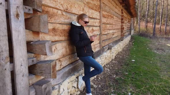 Thumbnail for Woman Using Smart Phone Near a Wooden House in an Old Village.
