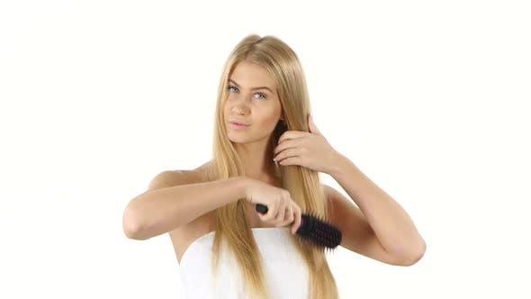 Hair. Beautiful Blond Brushing Her Hair. Hair Care, Bathroom