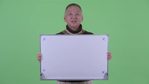 Thumbnail for Happy Mature Japanese Man Talking While Holding White Board