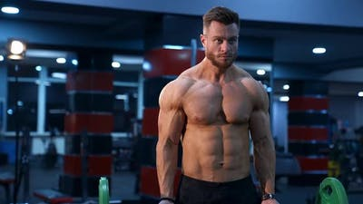 Handsome male athlete with perfect body trains with barbell in gym.
