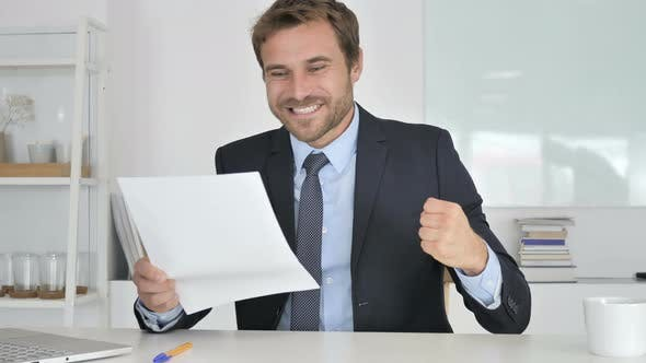 Thumbnail for Businessman Celebrating Success While Reading Documents