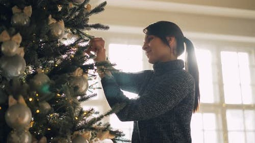 Smiling Student Is Decorating Artificial New Year Tree Hanging Silver Balls and Lights