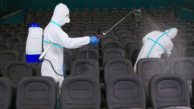 Two Men Cleaning Cinema By Spraying Disinfectant