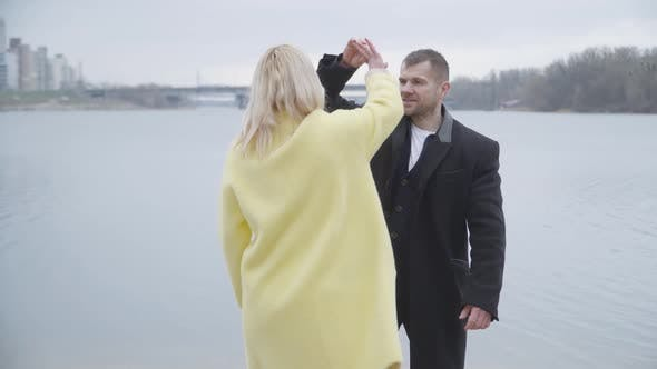 Happy Adult Couple Dancing and Hugging on Riverbank