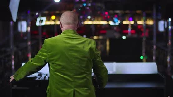 Rückansicht von fröhlichen alten kaukasischen Mann Tanzen und Spinning neben Musik Controller in Nachtclub
