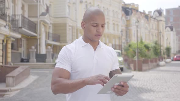 Thumbnail for Portrait of Handsome Confident Bald Middle Eastern Man Typing on the Tablet Standing on the Street