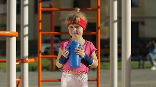Girl in Sportswear Drinking Water for Refreshment After Fitness Exercises. Little Athletic Child