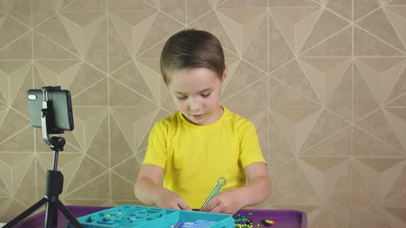 Junge, der Video anrufe verwendet, sagt Freunden und zeigt, wie er zu Hause Zeit verbringt. Das Kind lächelt und spricht