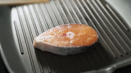 The Man's Hand Puts a Piece of Salmon on a Hot Frying Pan
