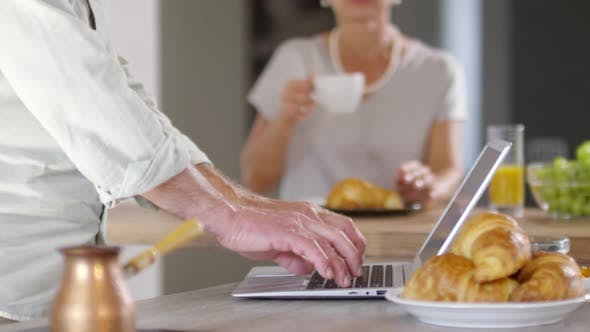 Thumbnail for Unrecognizable Man with Laptop and Woman Having Breakfast at Home