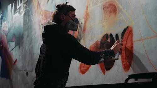 Young Man Painting Abstract Graffiti Outdoors