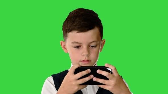 Konzentrierter Junge in der Weste mit Sprachbefehlen, um etwas auf seinem Telefon auf einem grünen Bildschirm zu sehen