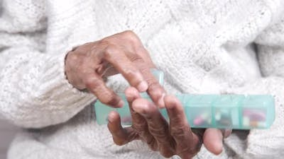 Senior Women Hand Taking Pill From a Pill Box