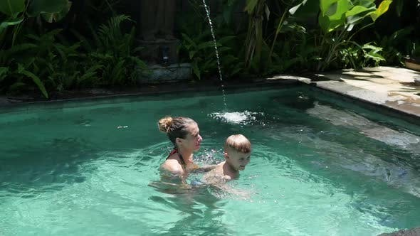 Little Boy Swims with Mom in the Pool on Vacation in Asia, Baby Swimming. Mom and Son Swim in the