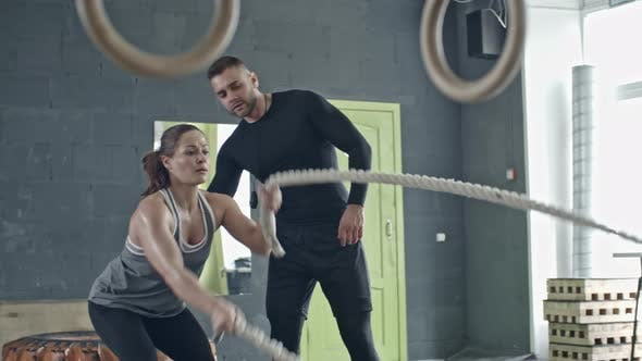 Thumbnail for Personal Coach Teaching Woman Doing Battle Rope Exercise