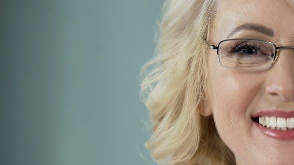 Thumbnail for Beautiful senior blonde with eyeglasses smiling into camera, health care