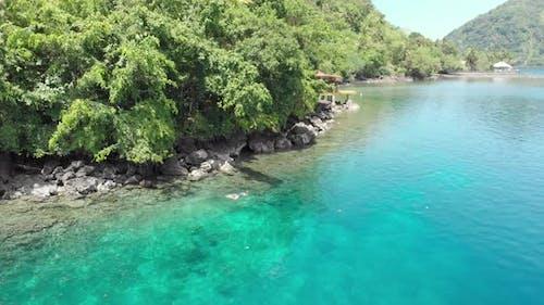 Aerial: woman snorkeling on Pulau Gunung Api coastline coral reef tropical carib