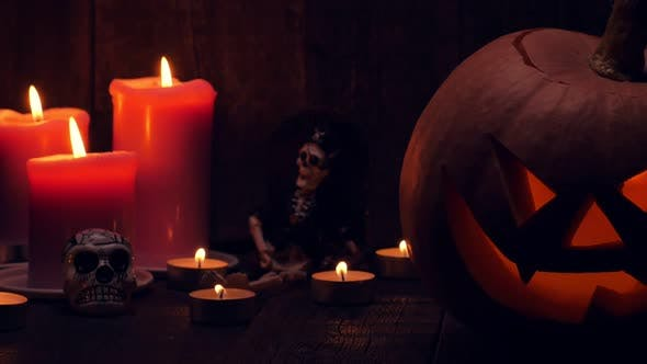 Thumbnail for Halloween Pumpkin with Scary Face and Candles on Wooden Background. Jack-o-lantern