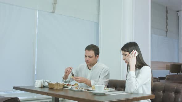 Thumbnail for Young Man Eating While His Girlfriend Talking on the Phone at Restaurant
