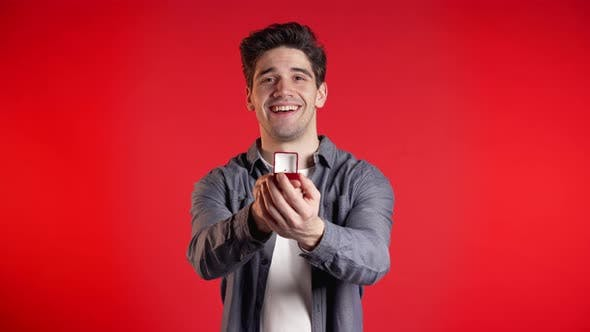 Thumbnail for Young Handsome Guy Holds Out Jewelry Box with Wedding Ring To the Camera