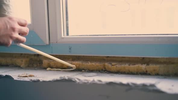 Builder wendet Sprühschaum-Isolierung auf die Fensterbank an
