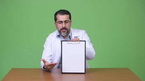 Handsome Persian Bearded Man Doctor Talking While Showing Clipboard