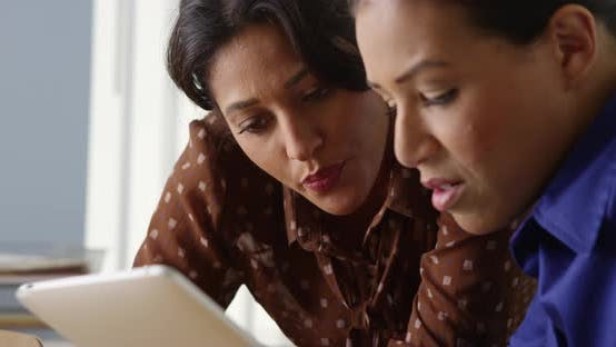 Thumbnail for Close up of two Black and Hispanic business women working on tablet computer