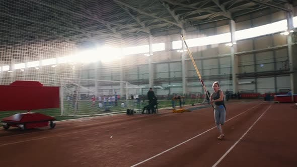 Thumbnail for Pole Vault Training - a Young Woman with Ponytail Running Up and Jumping Over the Bar - Touches the