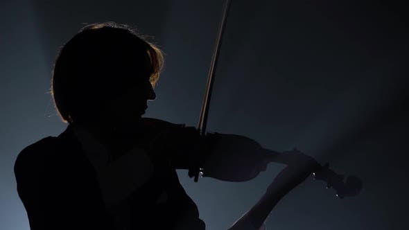 Thumbnail for Violinist Performing in a Dark Studio with a Lantern. Black Background. Silhouette