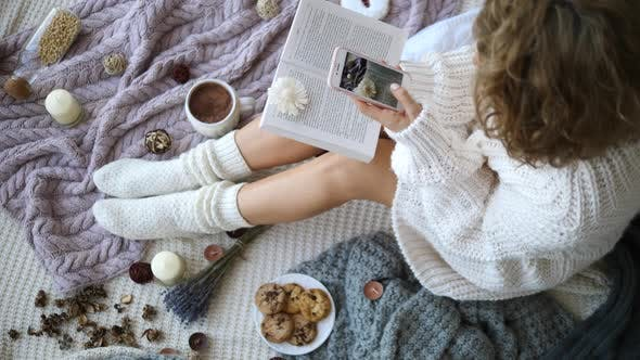 Thumbnail for Woman Taking Photo With Cellphone Of Flat Lay With Knitted Socks, Cup And Book