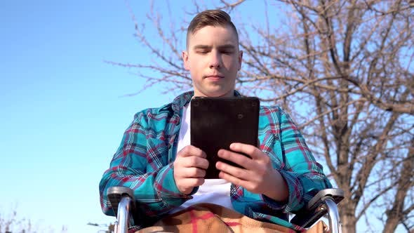 Cover Image for Young Man on a Wheelchair with a Tablet. Disabled Man in Nature Is in Correspondence on a Tablet.