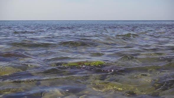 Thumbnail for Kleine Wellen rollen auf einem Felsen im Wasser auf dem Ufer