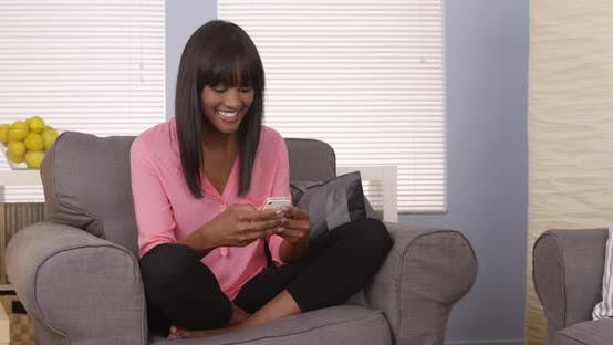 Thumbnail for Black woman using smartphone at home