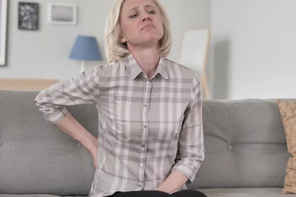 Old Woman With Back Pain Sitting On Couch By Stockland On Envato
