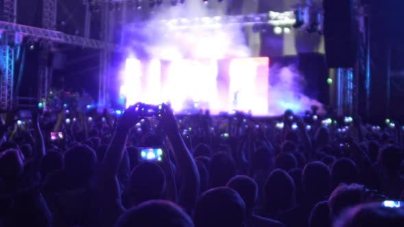 Cover Image for Devoted Fans Filming Favorite Band Performance on Mobile Phones, Saving Memories