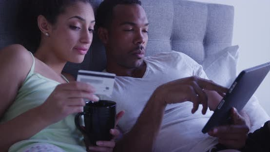 Thumbnail for Black and Hispanic couple making online purchase with tablet computer browsing the internet in bed