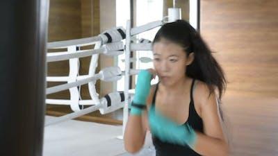Asian Woman Kick Boxer Punching Bag in Gym
