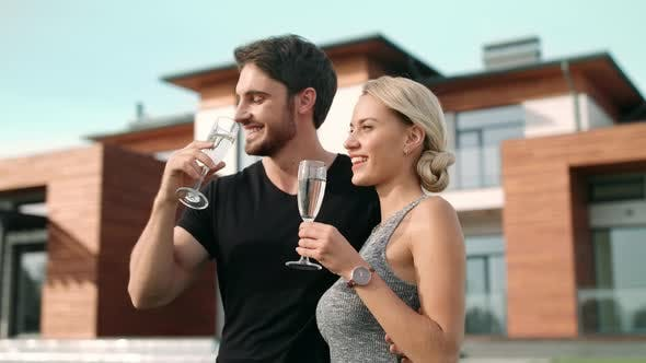 Thumbnail for Lovely Couple Toasting Champagne Near Luxury Apartments