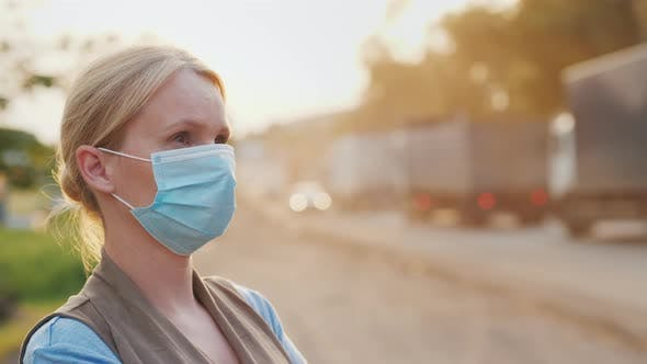 Thumbnail for A Woman in a Protective Mask on a Dusty Road