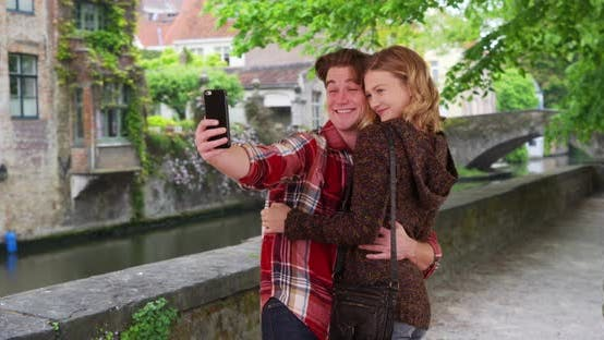 Thumbnail for Cheerful millennial couple taking a selfie with smartphone, smiling and laughing