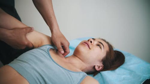 Woman Having an Osteopathic Treatment - the Doctor Massaging Her Shoulder