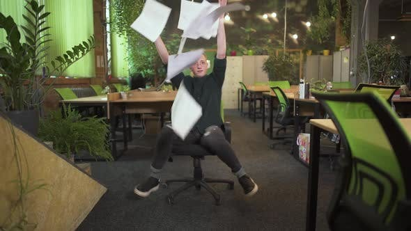 Thumbnail for Young Man in Glasses Spinning on an Office Chair and Throwing Up Papers in Modern Office Decorated