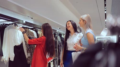 Girl Tries on a Dress and Consults with Friends in the Store