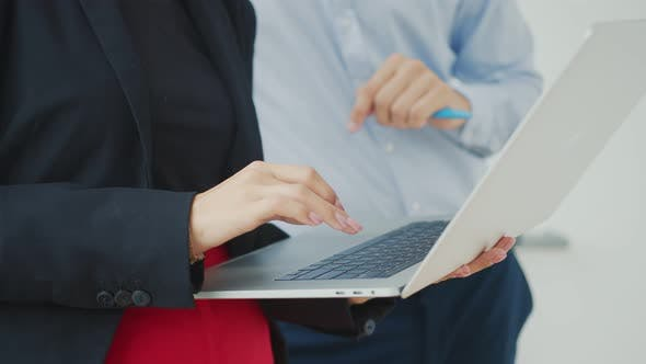 Thumbnail for Woman Holding a Laptop and Pressing Laptop Keys in the Office with Another Employee.