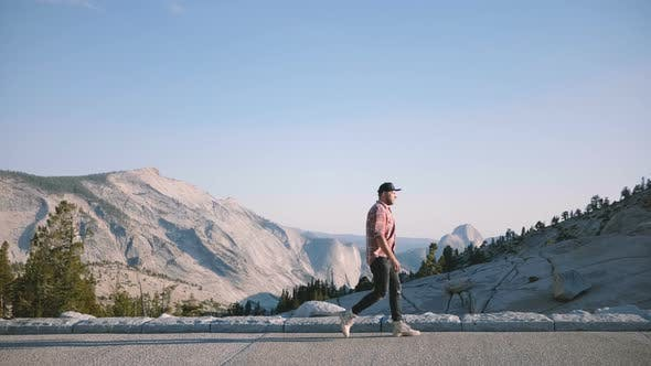 Successful Man Walking Along Epic Mountain Scenery View at Sunny