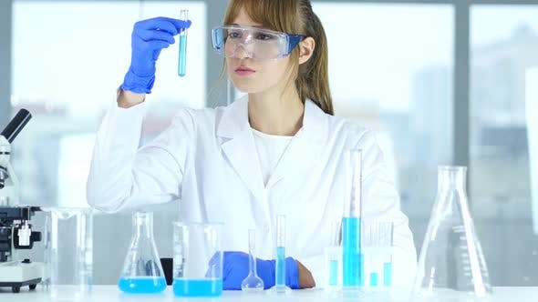 Thumbnail for Female Research Scientist Looking at Blue Solution in Test Tube in Laboratory