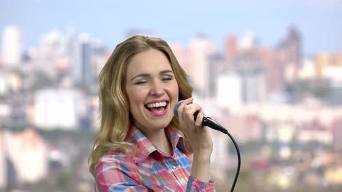 Emotional Young Woman Singing Into Microphone