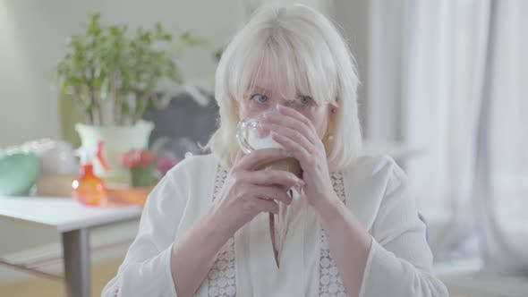 Thumbnail for Beautiful Caucasian Mature Woman with Blond Hair and Grey Eyes Drinking Coffee and Looking Away